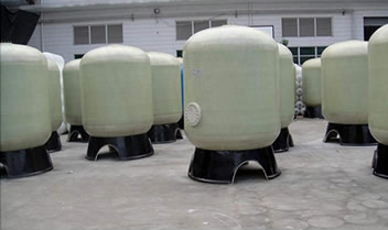 Several FRP sand filtration tanks are placed on the floor waiting for package.