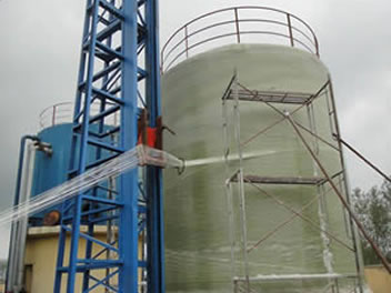 A vertical filament winding machine is winding structural layers of FRP tanks.
