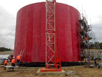 There is one red vertical tank moulding on the jobsite, and many workers are installing the mould.