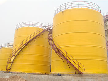 It shows three yellow vertical FRP tanks and they are installed with spiral ladders.